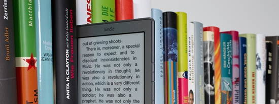 Shelf of books with a tablet reader .